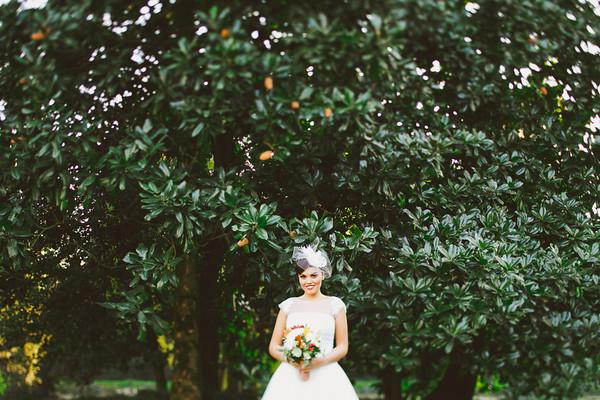 sposa nel giardino sotto magnolia in abiti vintage